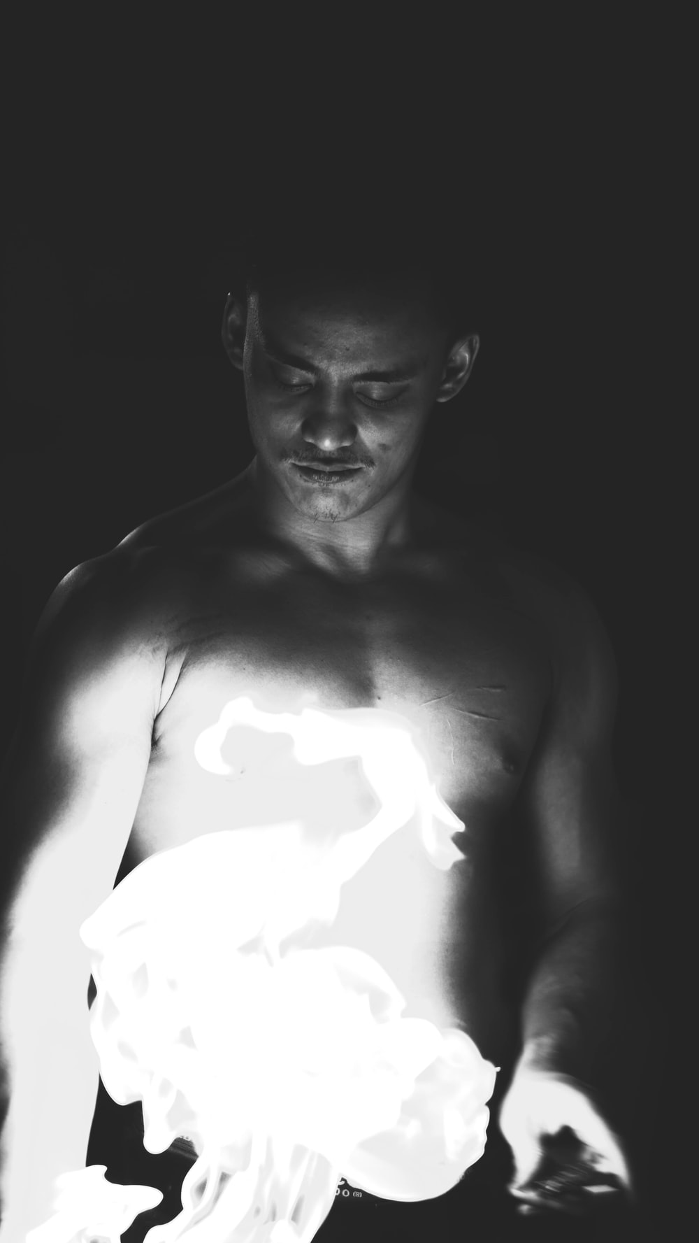 topless man smoking cigarette in grayscale photography