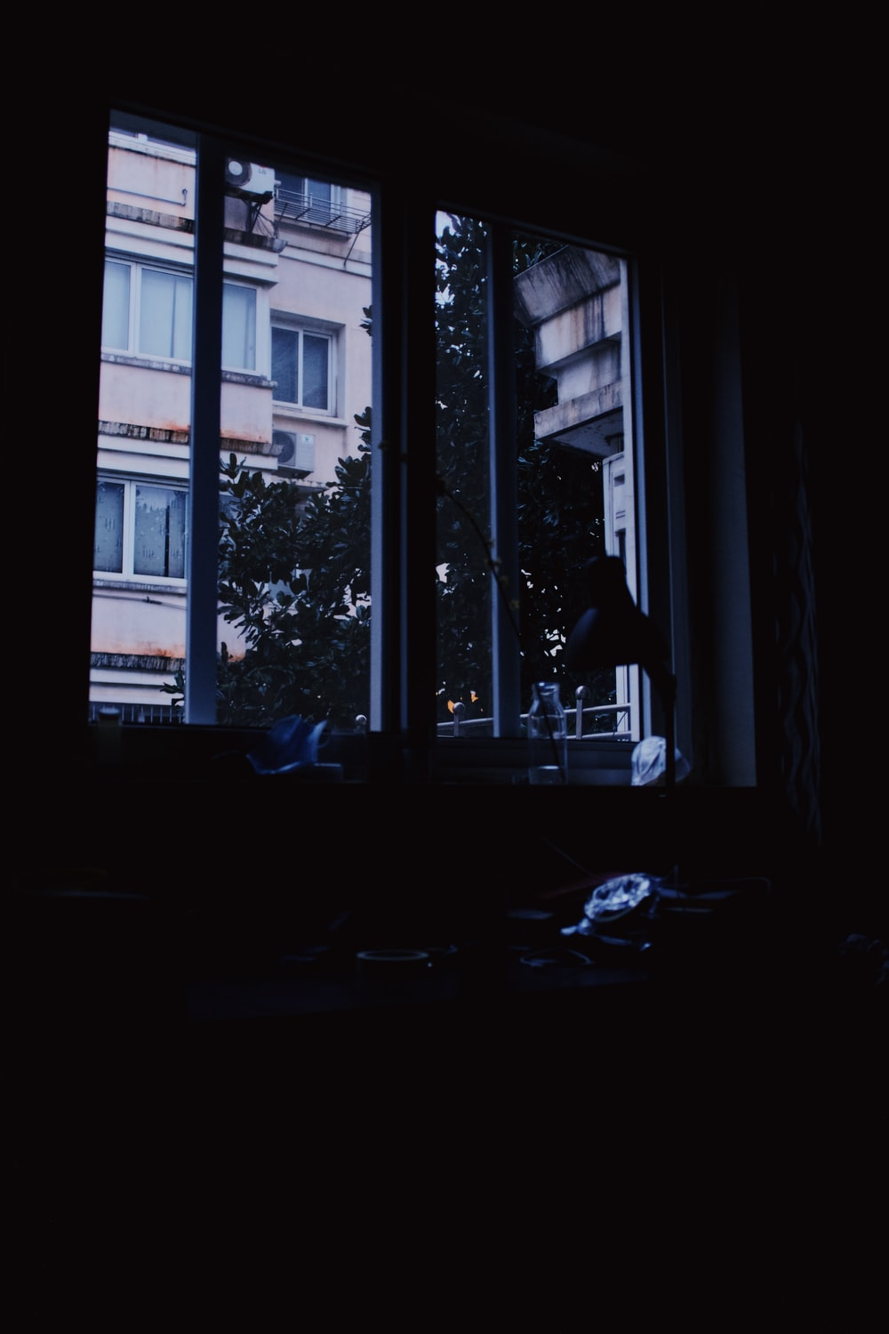 silhouette of person sitting on floor near window during daytime