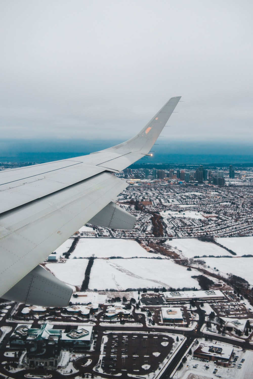 white airplane wing over city during daytime