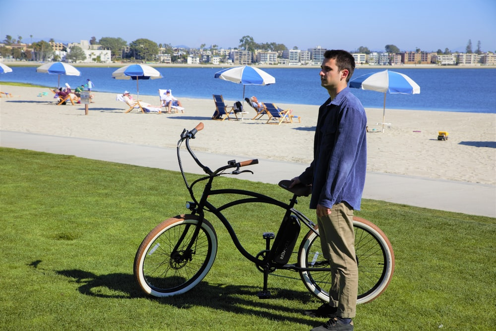 man in blue dress shirt riding on black bicycle on green grass field during daytime