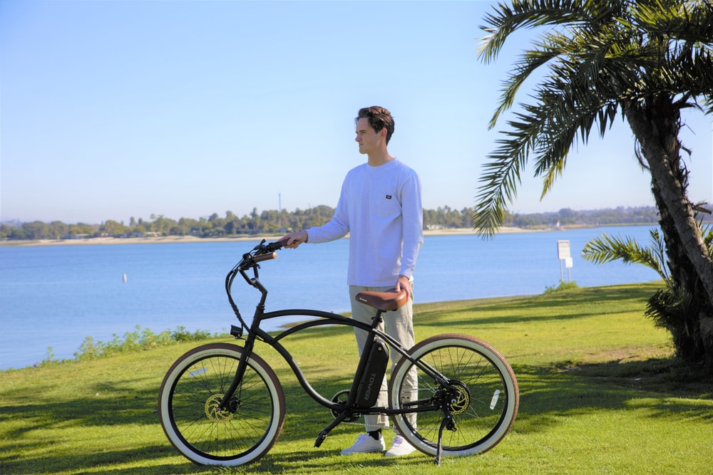 man in white long sleeve shirt riding black bicycle on green grass field during daytime