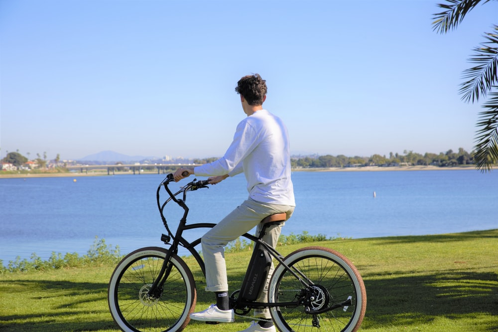 man in white long sleeve shirt riding on black bicycle near body of water during daytime