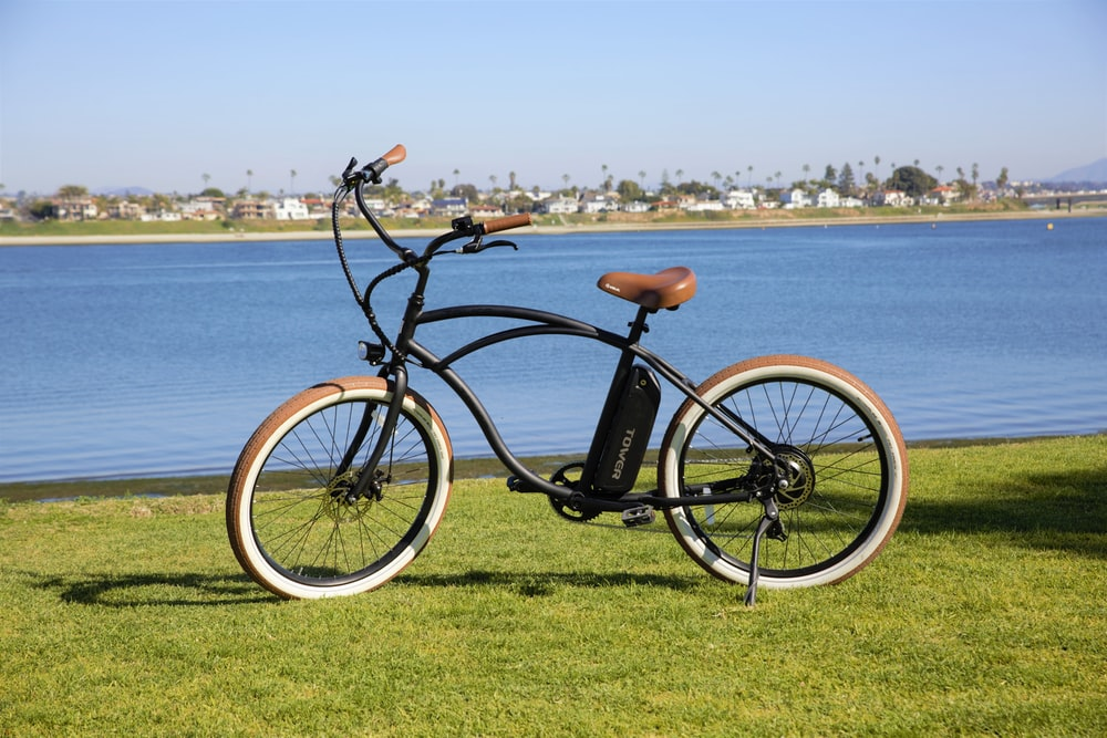 black commuter bike on green grass field near sea during daytime