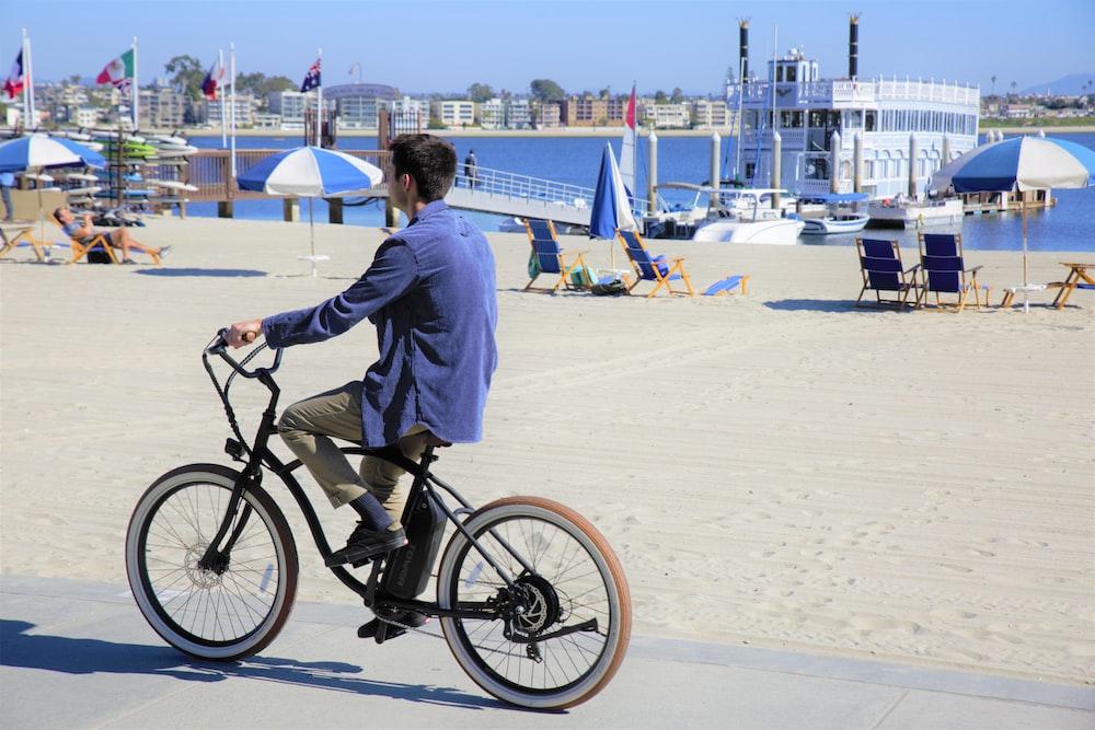 man in white dress shirt riding on black bicycle on white sand during daytime