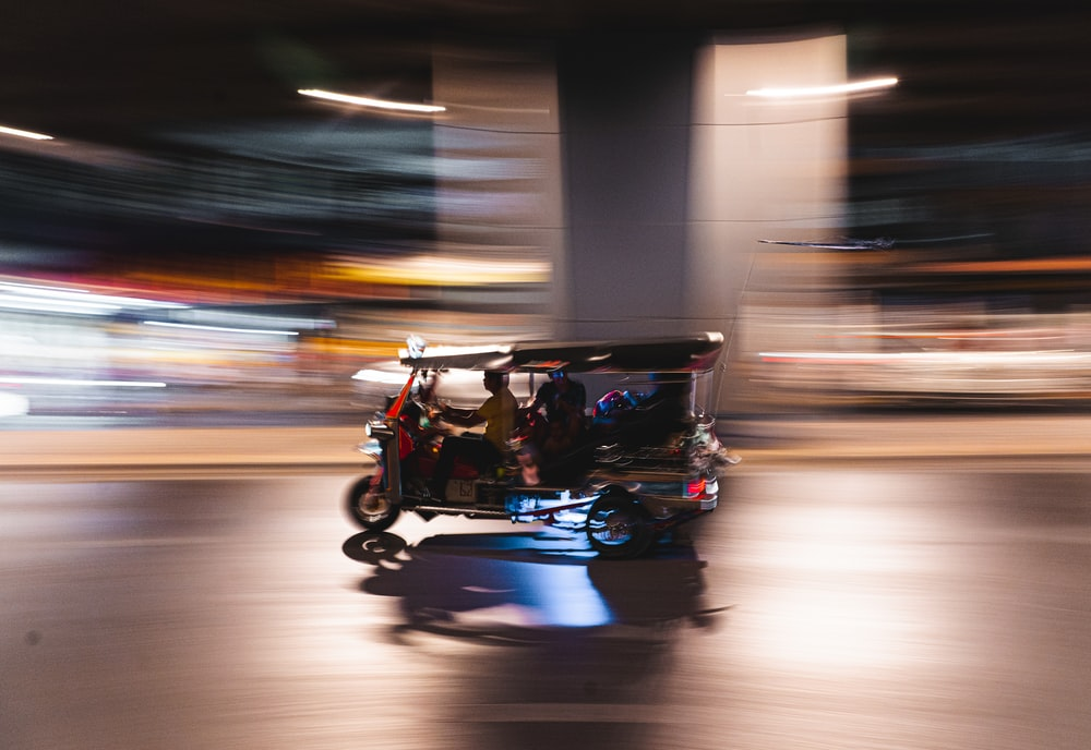 man in black jacket driving blue and black auto rickshaw