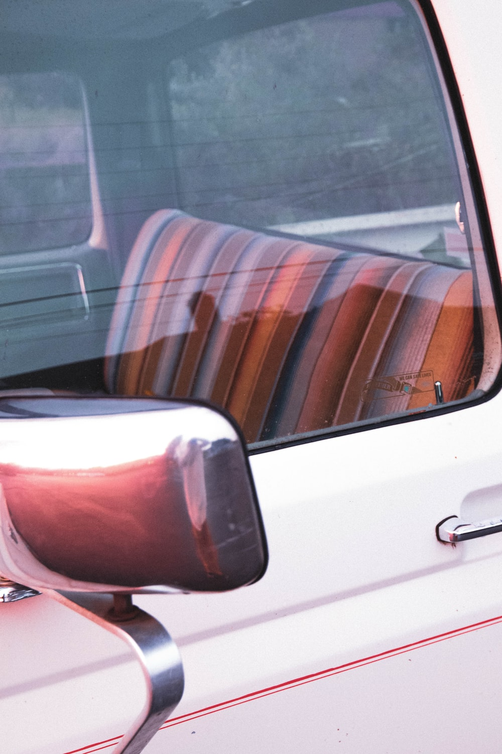 white car door with brown and white striped seat