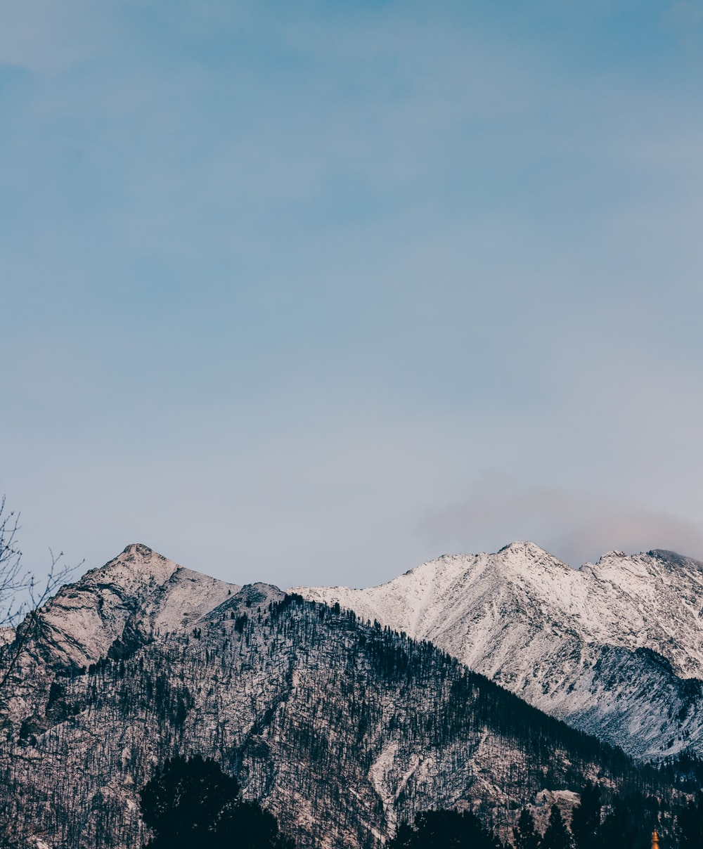snow covered mountain under gray sky