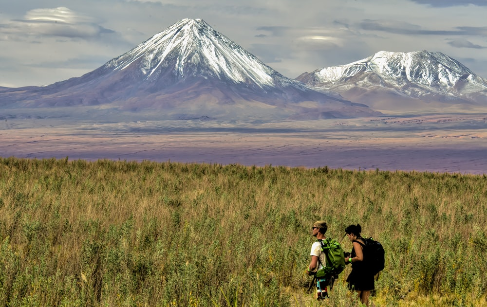 man and woman sitting on grass field near mountain during daytime