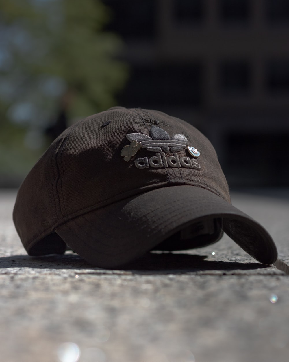 brown and black fitted cap on grey concrete floor