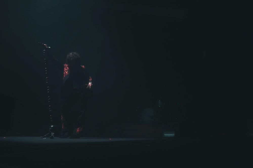 man in black jacket singing on stage