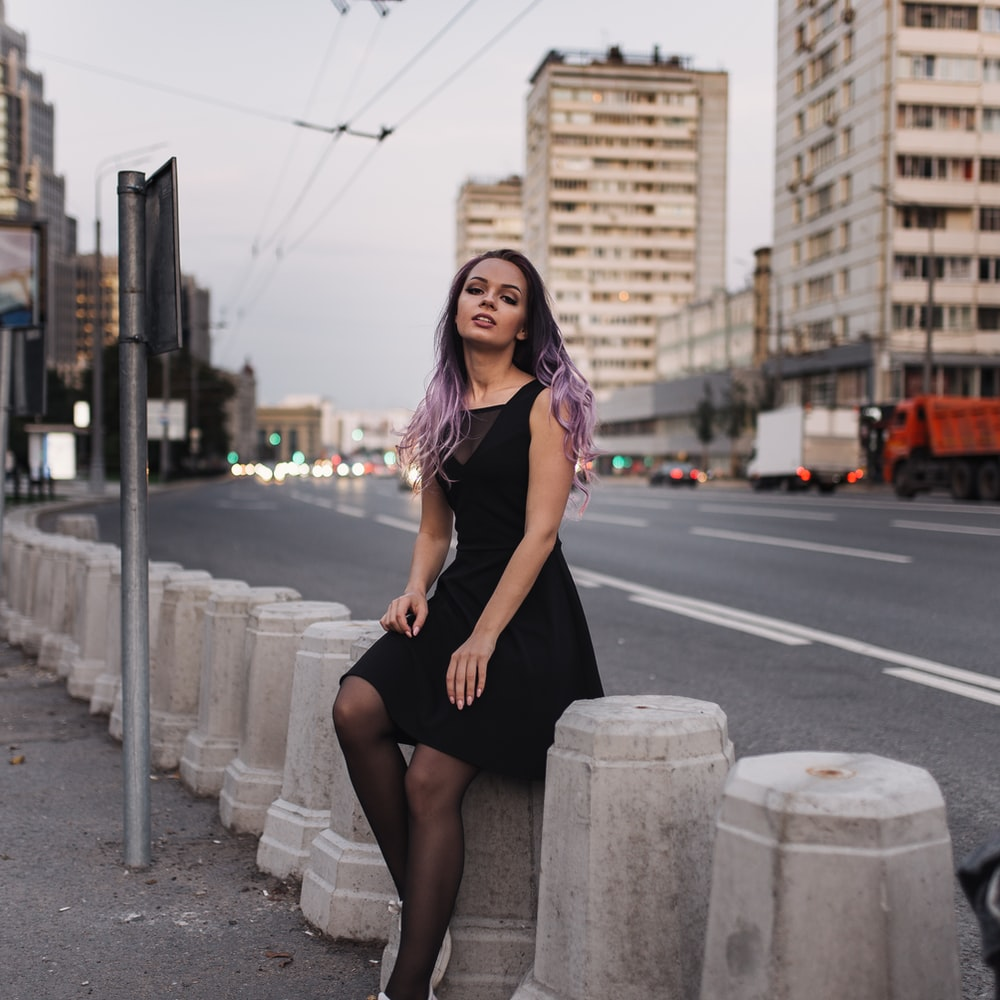 woman in black dress sitting on gray concrete post during daytime
