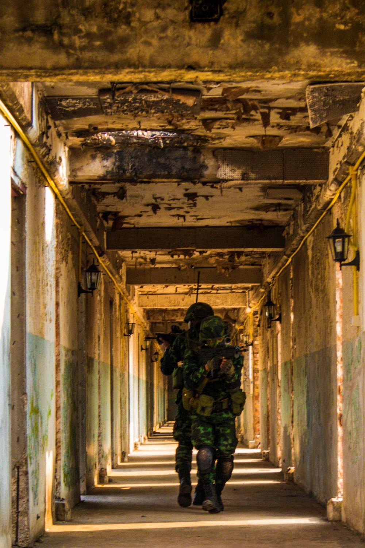 man in green jacket standing on hallway