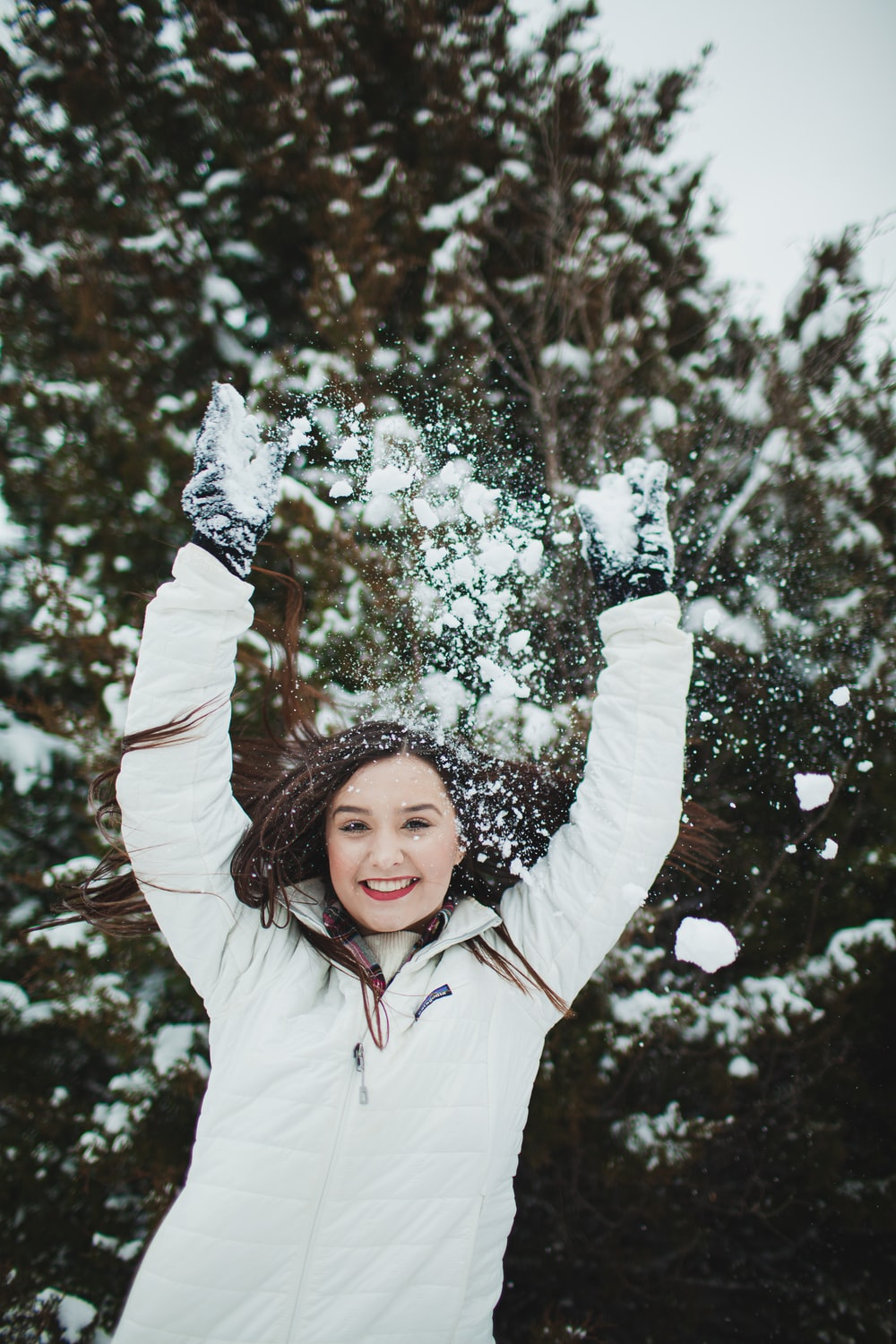 girl in white jacket standing near tree with snow