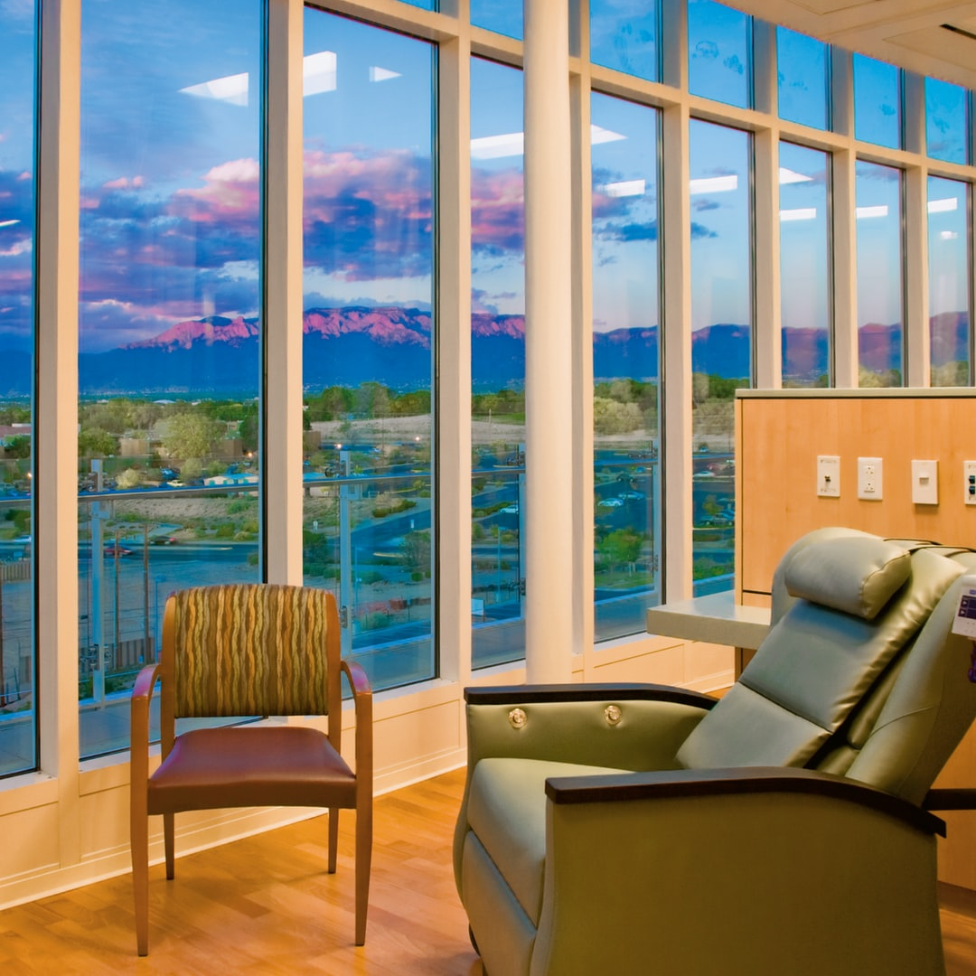 The chemotherapy infusion suite with a view of the Sandia Mountains at the University of New Mexico Cancer Center (UNMCC) in Albuquerque. Since first achieving National Cancer Institute designation in 2005, UNMCC and its consortium institutions -- Lovelace Respiratory Research Institute, Los Alamos National Laboratory, and Sandia National Laboratories -- have built a single transdisciplinary cancer-focused research enterprise and statewide networks for cancer care delivery and community participatory research.
