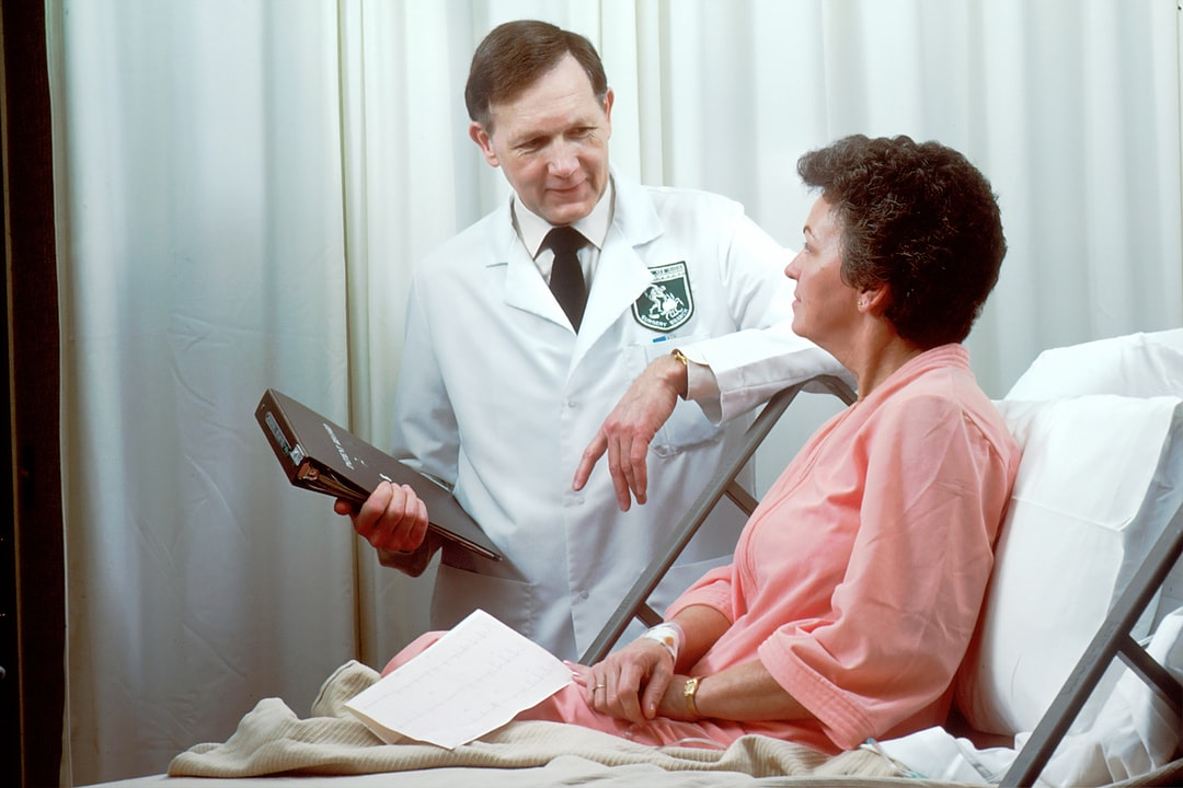 A Caucasian male doctor from the Oncology Branch consults with a Caucasian female adult patient, who is sitting up in a hospital bed.