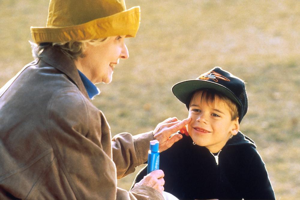 boy in black hat holding blue plastic bottle