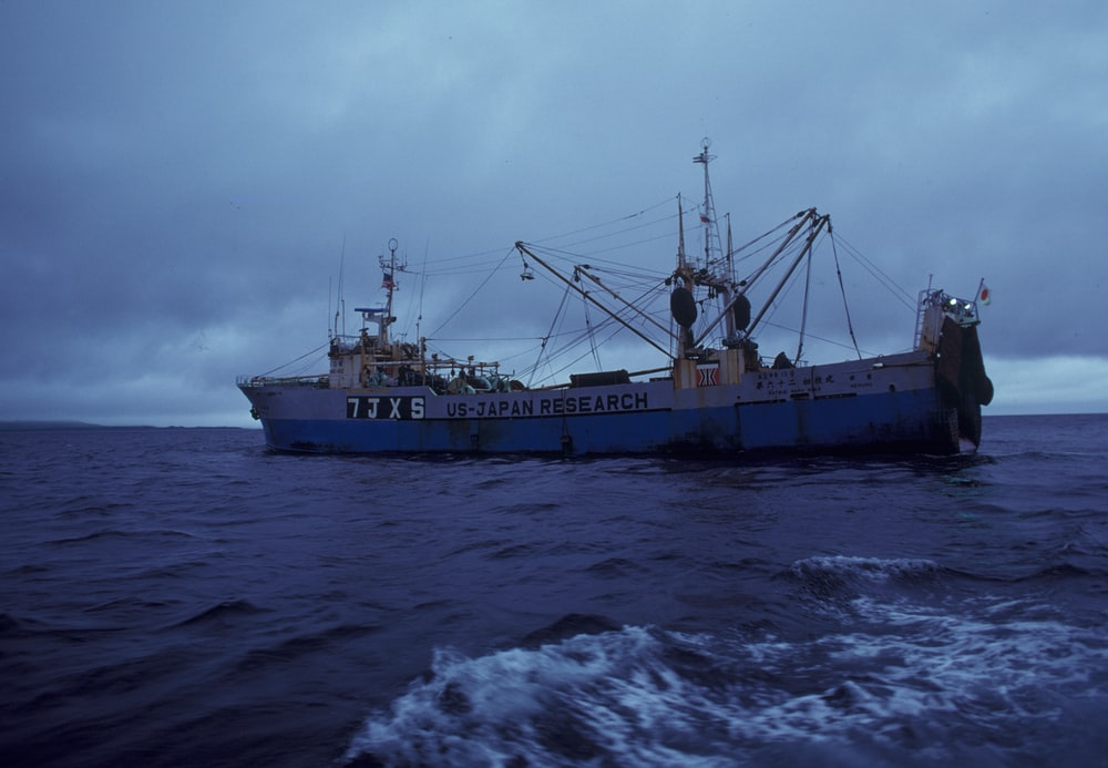 brown ship on sea under white clouds during daytime