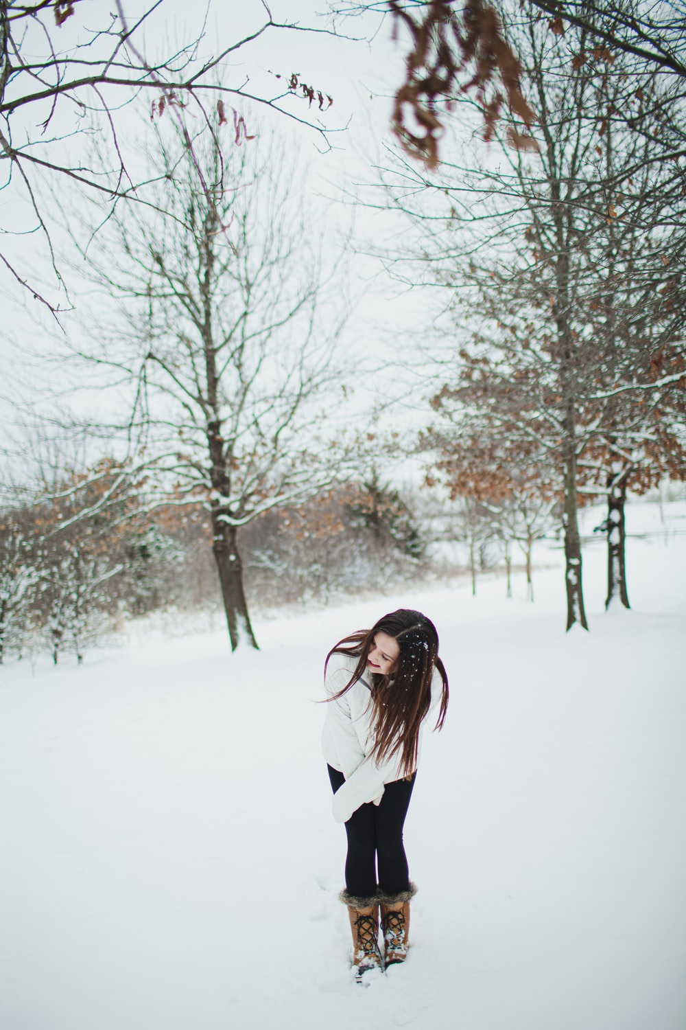 woman in black and white long sleeve shirt standing on snow covered ground during daytime