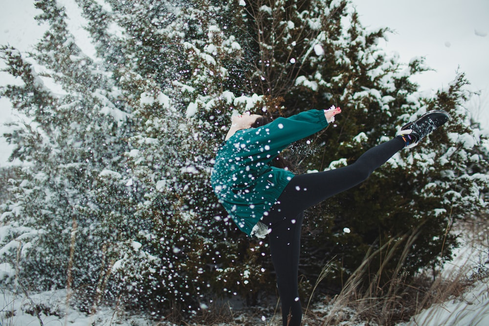 woman in green and black polka dot shirt and black pants standing on snow covered ground