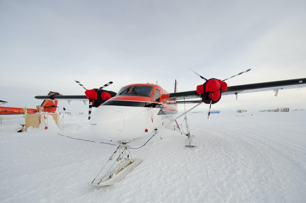 red and white helicopter on snow covered ground