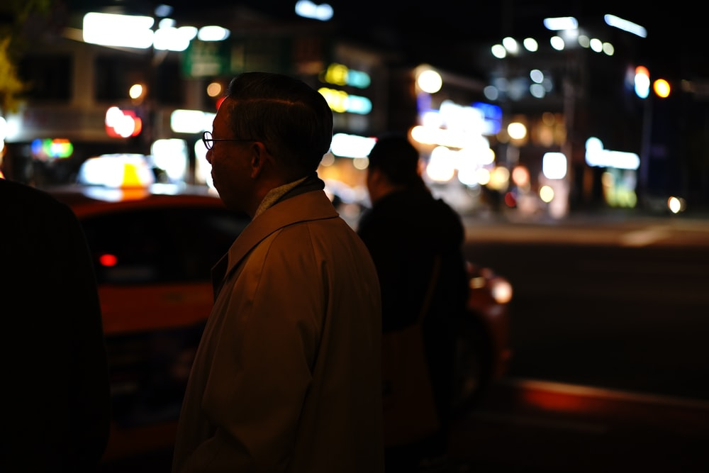 man in white coat standing near road during night time