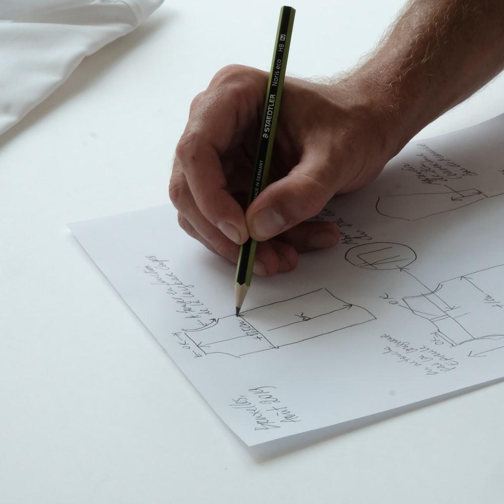 person holding black pencil on white printer paper