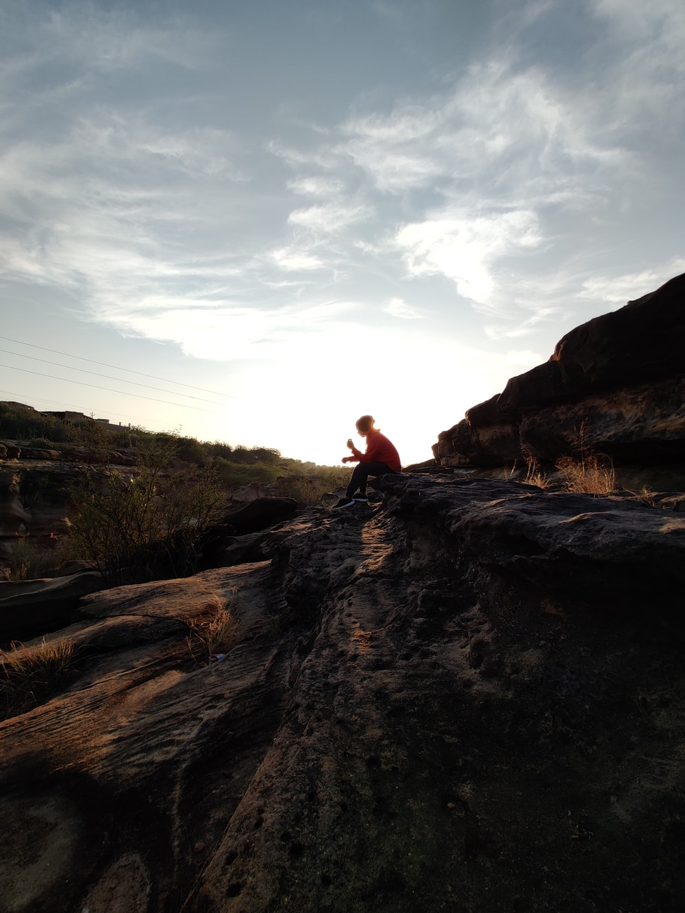 person sitting on brown rock formation during daytime