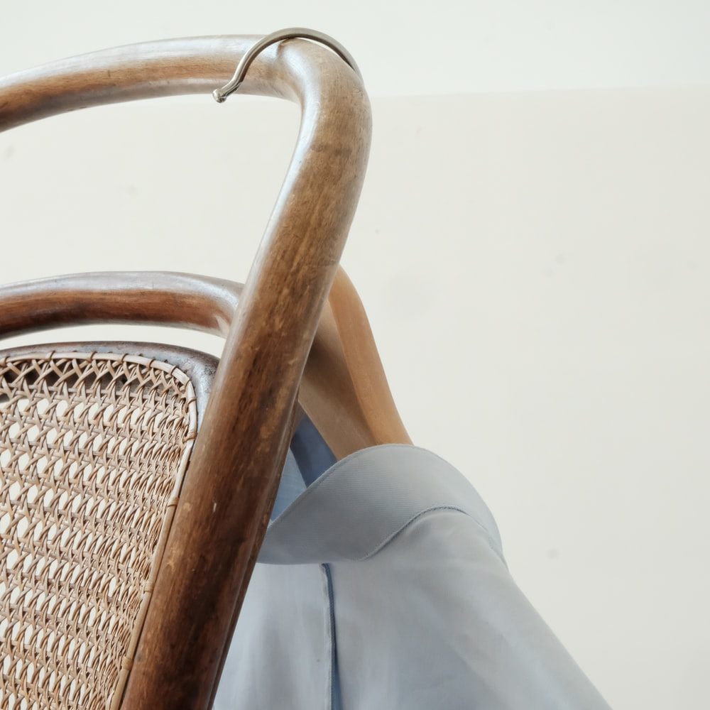 person in gray pants sitting on brown woven chair