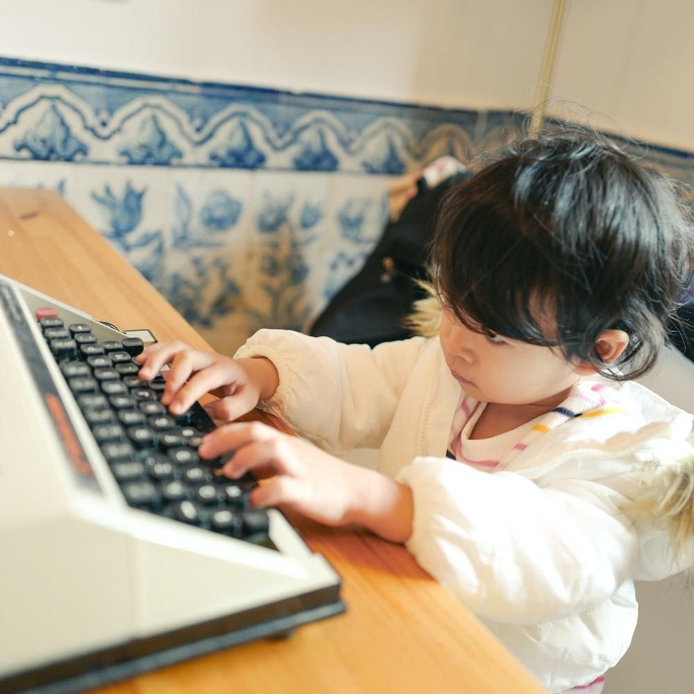 child in white long sleeve shirt using macbook pro