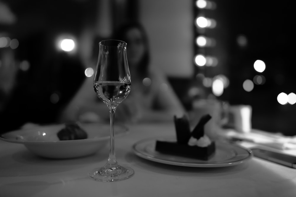 grayscale photo of wine glass on table