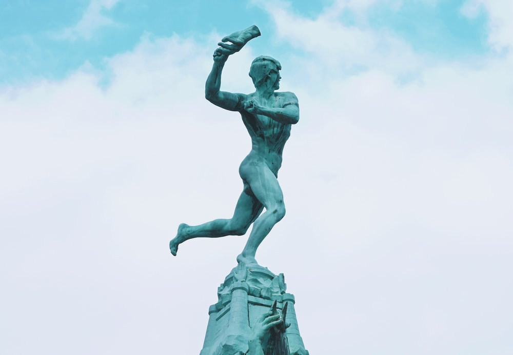 statue of man holding book under white clouds during daytime