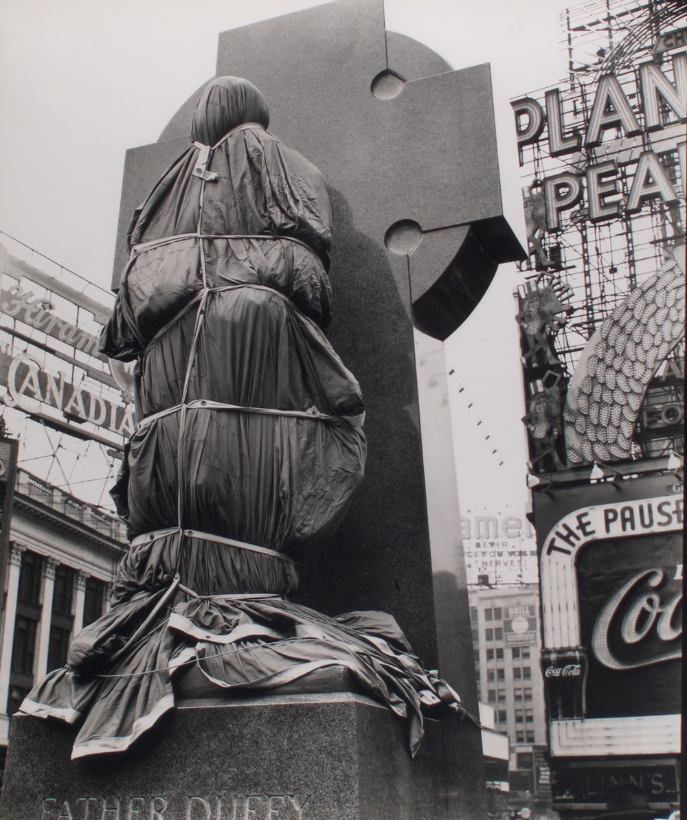 grayscale photo of man in black jacket statue