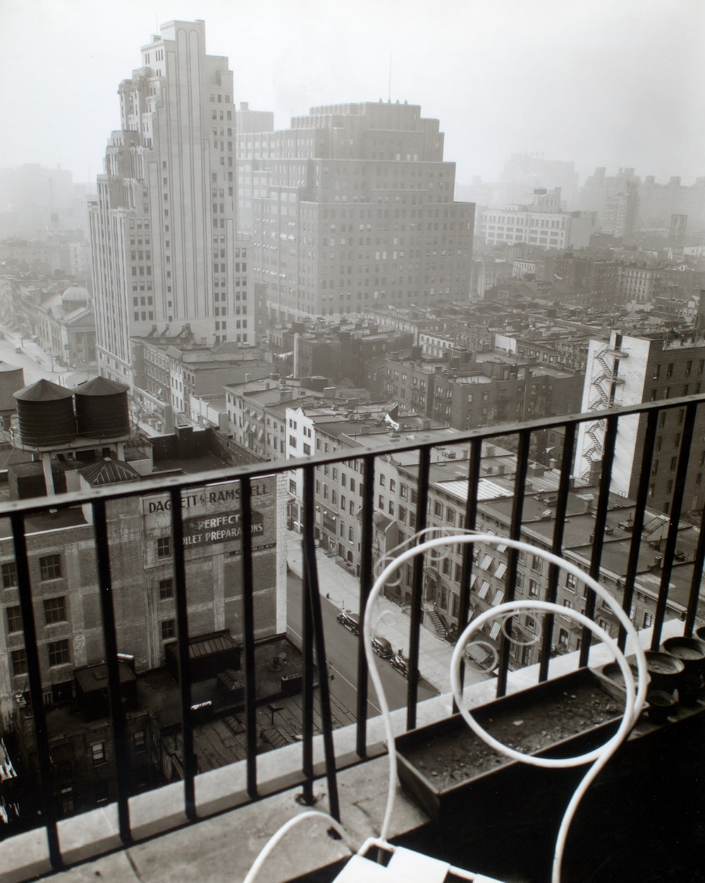 small balcony with white chair near city buildings during daytime