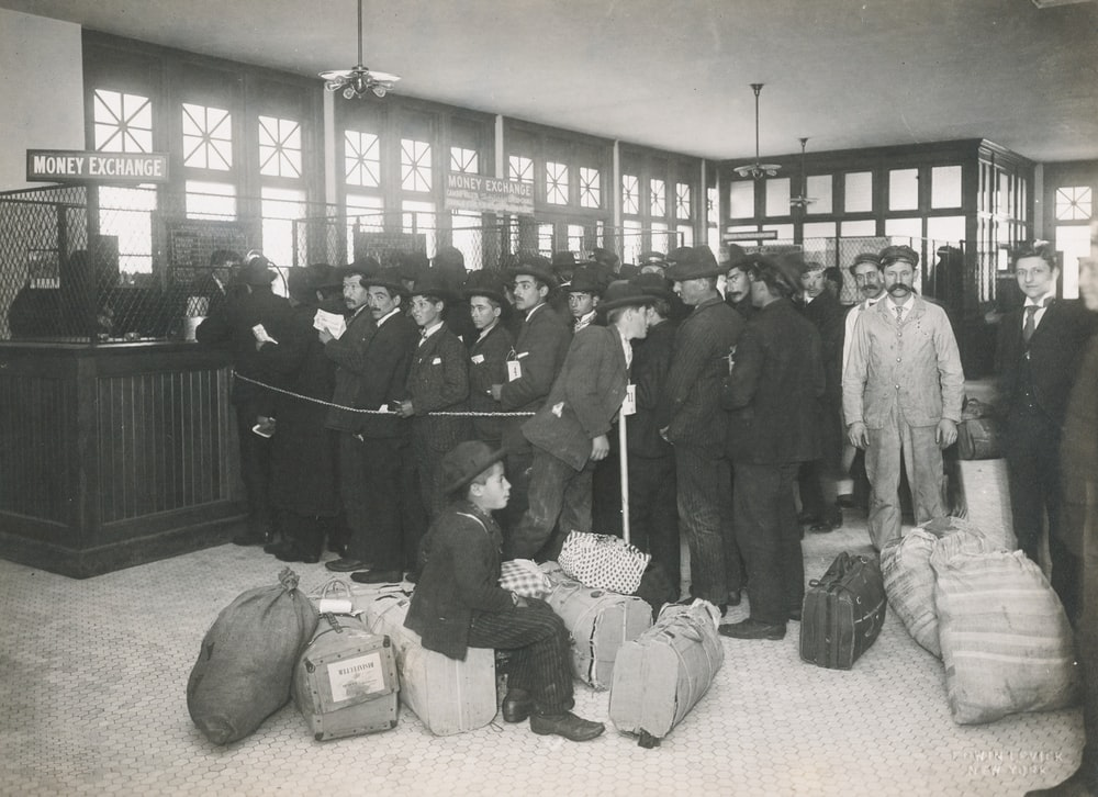 grayscale photo of a group of immigrants with bags inside