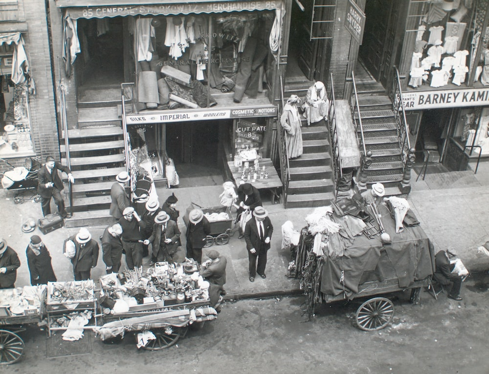 grayscale photo of people in front of car