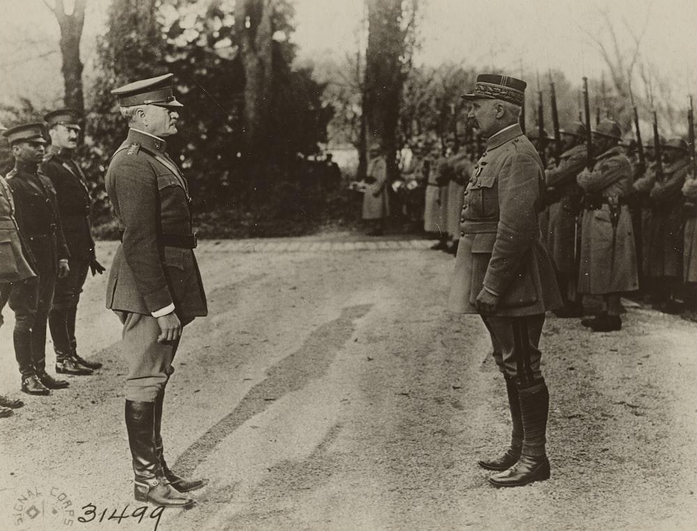 grayscale photo of 2 men in police uniform walking on street