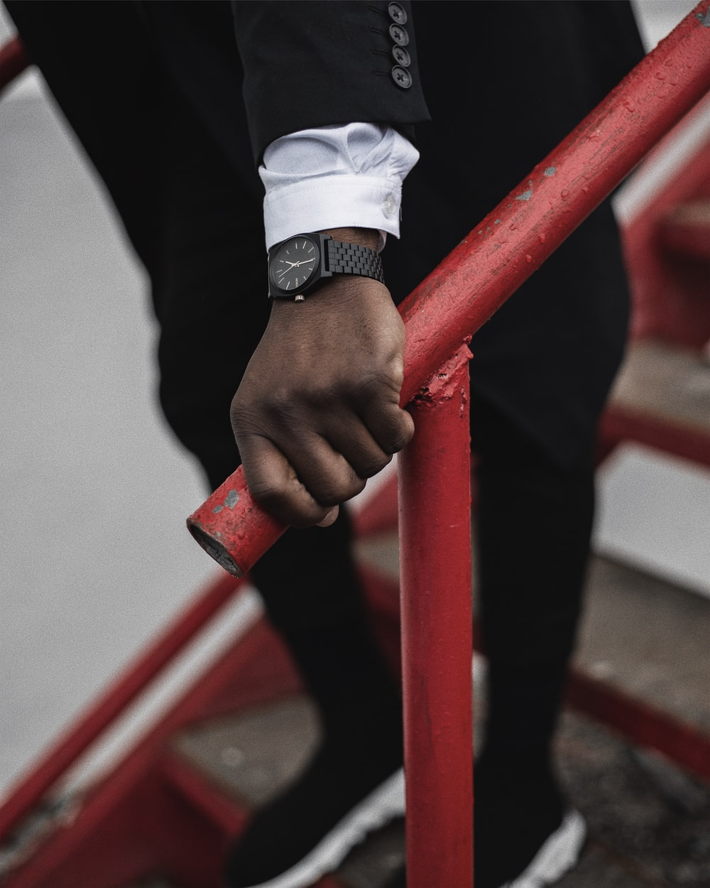 person wearing silver link bracelet watch holding red metal bar