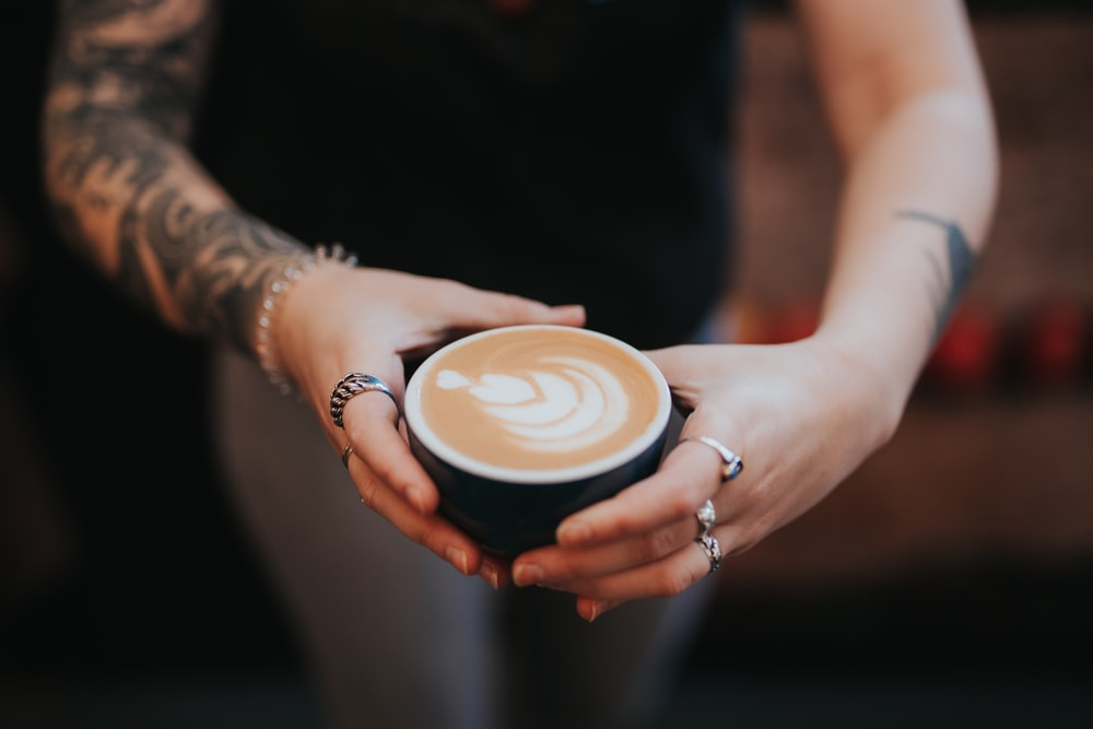person holding white ceramic cup with cappuccino