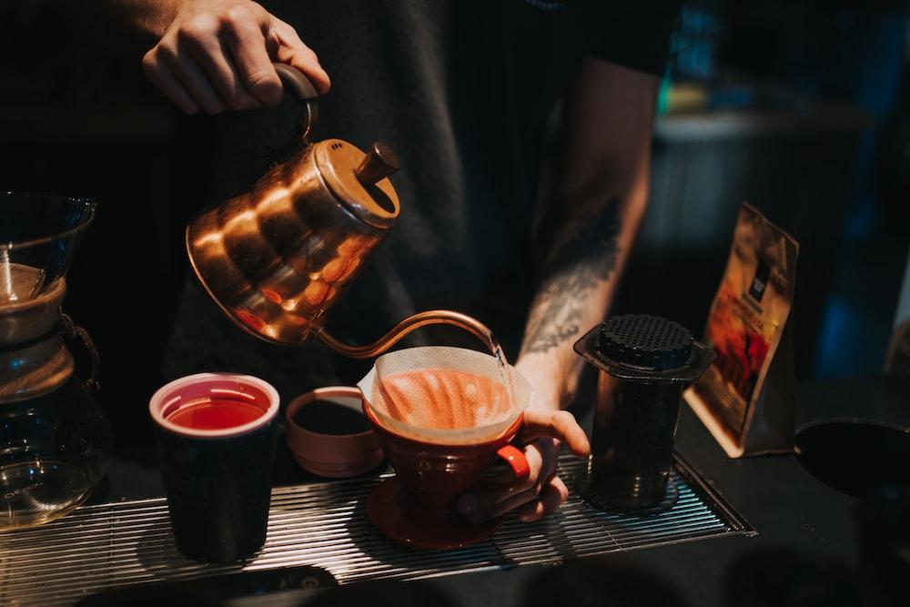 person pouring coffee on brown ceramic mug