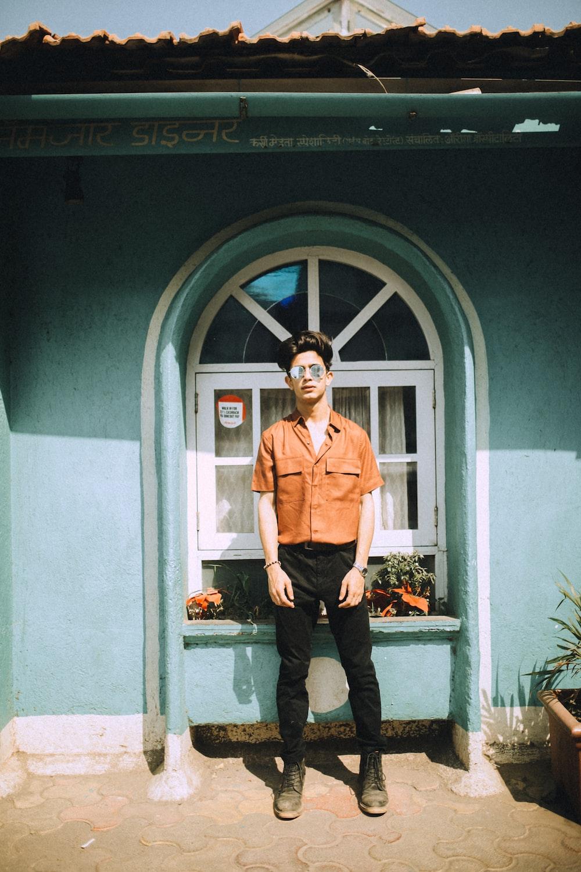 man in brown button up shirt and black pants standing beside blue wooden door