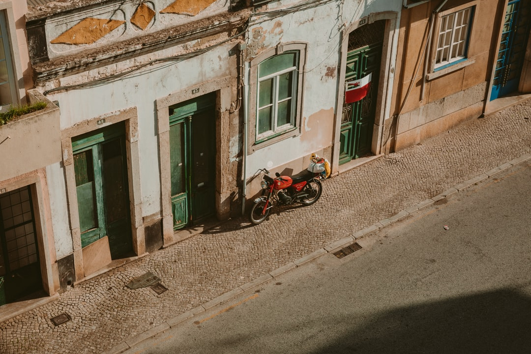 Old Red Motorcycle In A Downtown Street - unsplash