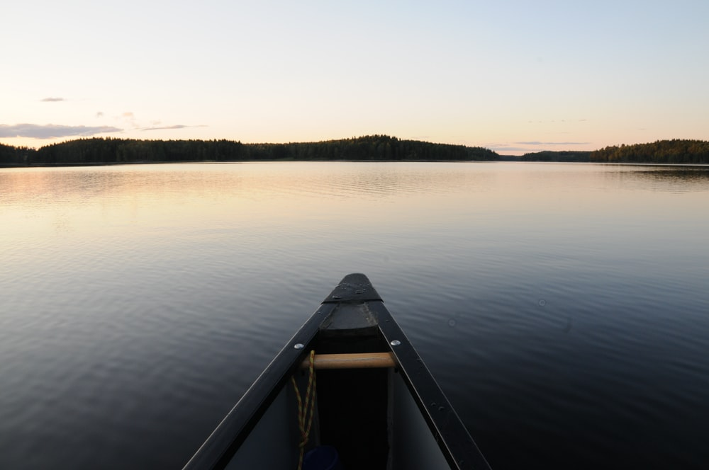 brown wooden boat on lake during daytime