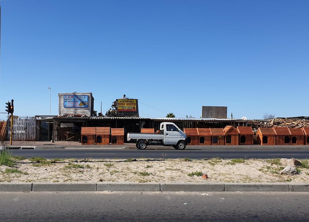 white sedan parked beside brown building during daytime