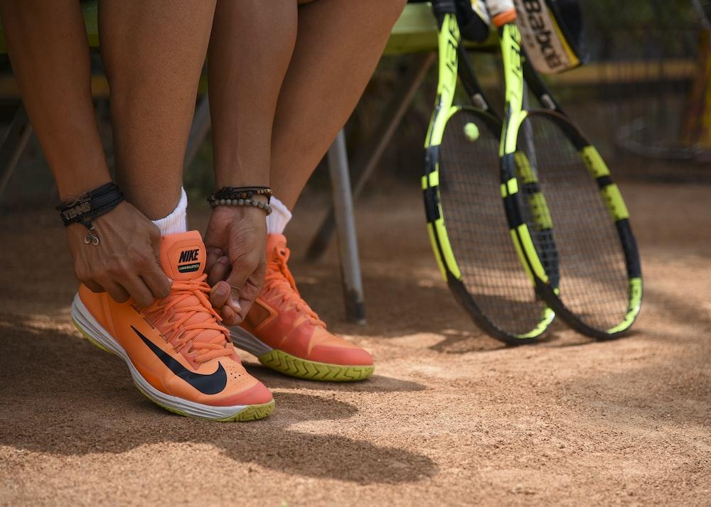 person wearing orange nike sneakers