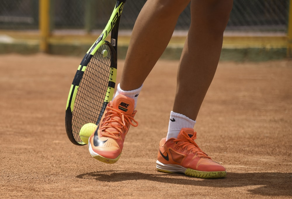 person in red nike shoes holding tennis racket