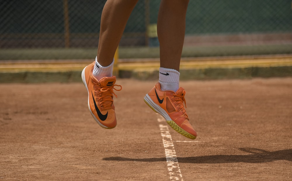 person in red nike sneakers jumping on field