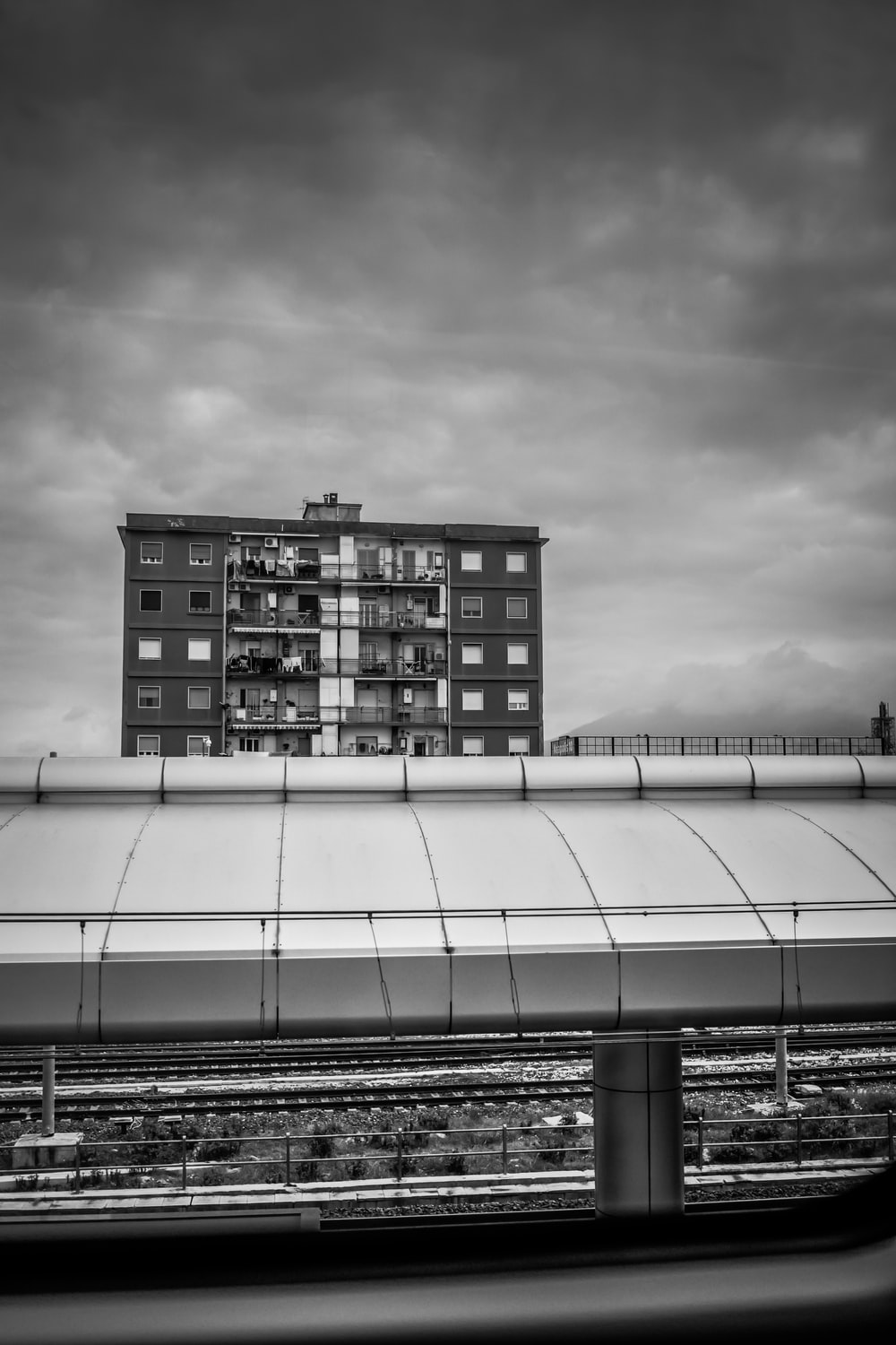 grayscale photo of building under cloudy sky