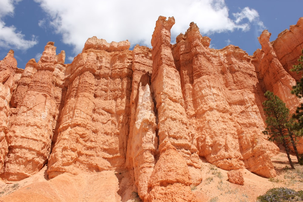 brown rock formation under blue sky and white clouds during daytime