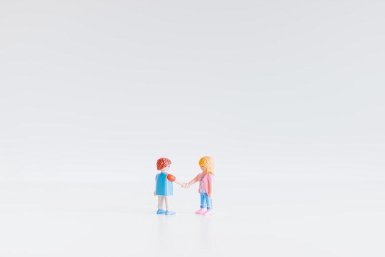 Photo of two toy figures shaking hands, by Paweł Czerwiński