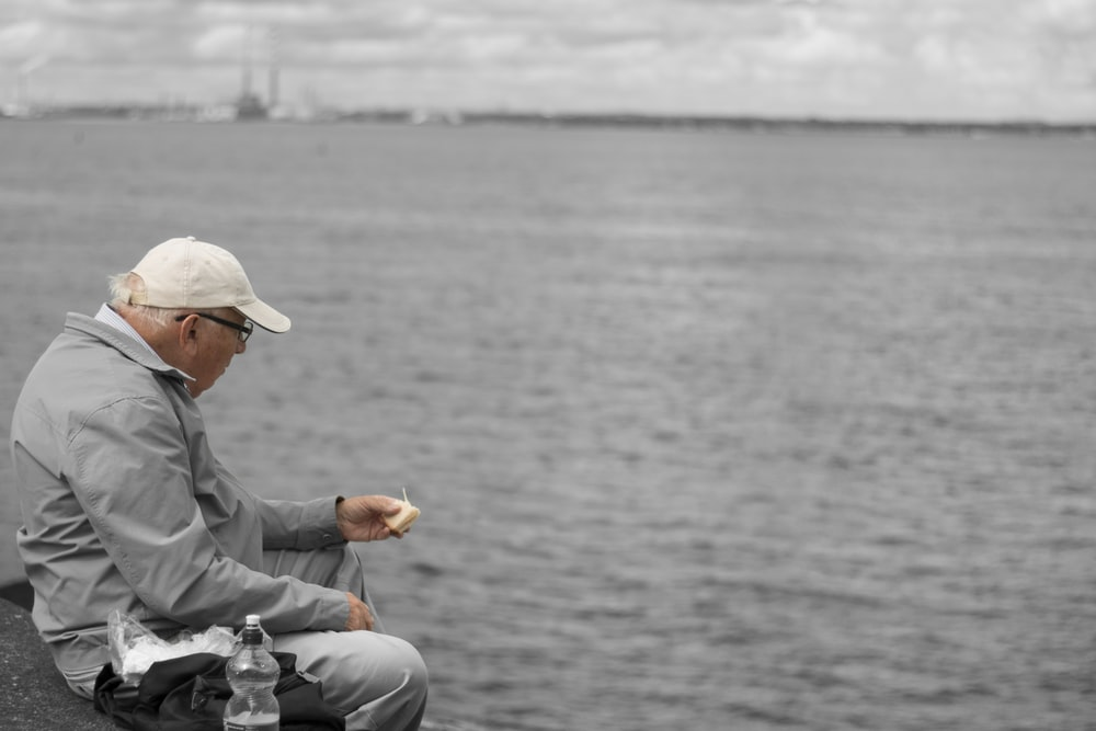 man in gray dress shirt and white pants sitting on gray rock near body of water